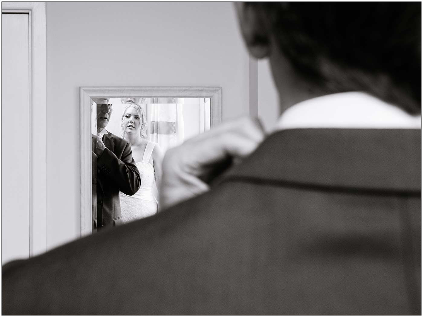 Bride watching father in mirror
