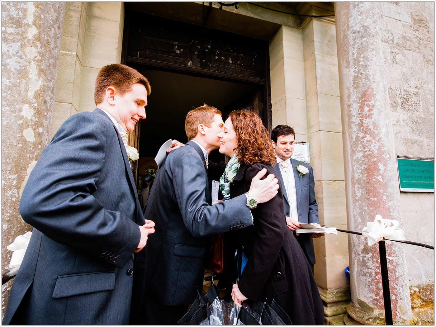 Groom welcomng guests to St James D'Eivile church by Walton Hall