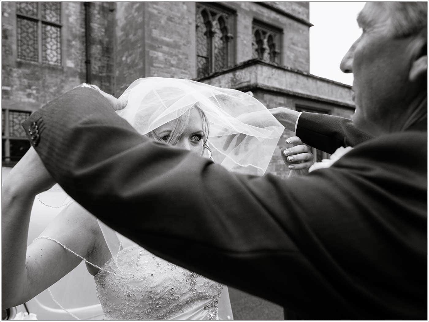 Father helping bride with veil as theyarrive at St James D'Eivile church