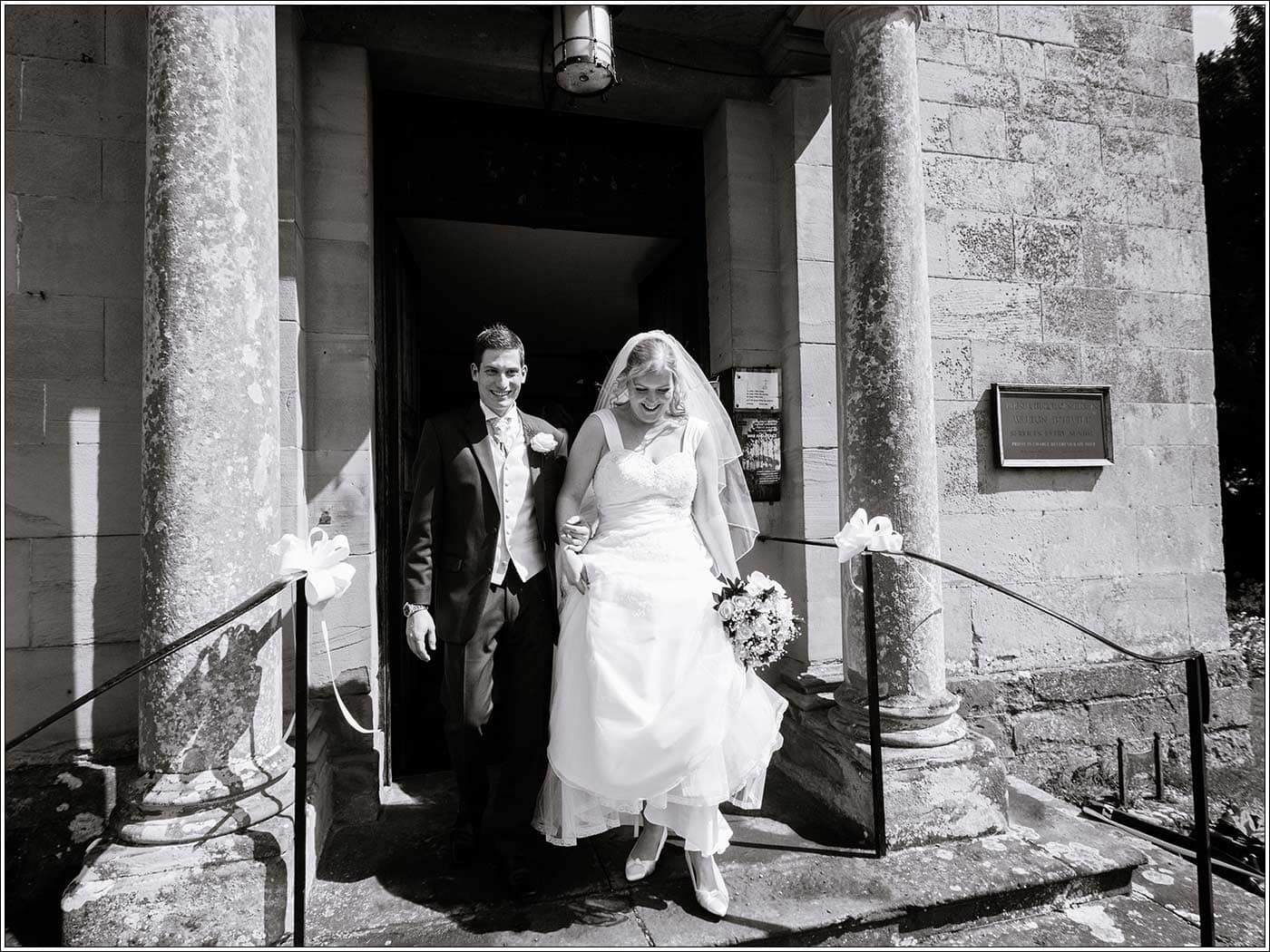 Bride and groom exiting wedding at St James D'Eivile Church by Walton Hall