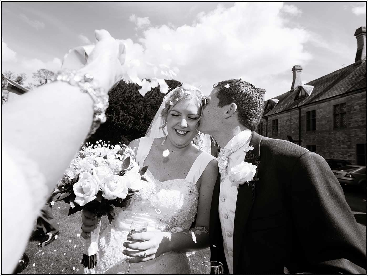 Groom kissing bride during confetti time at Walton Hall