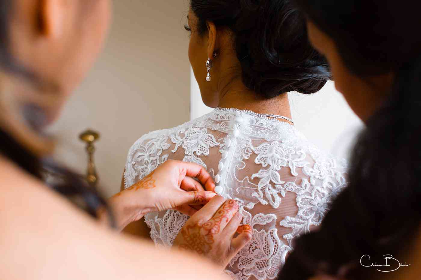 Bride having her dress buttoned by her maids