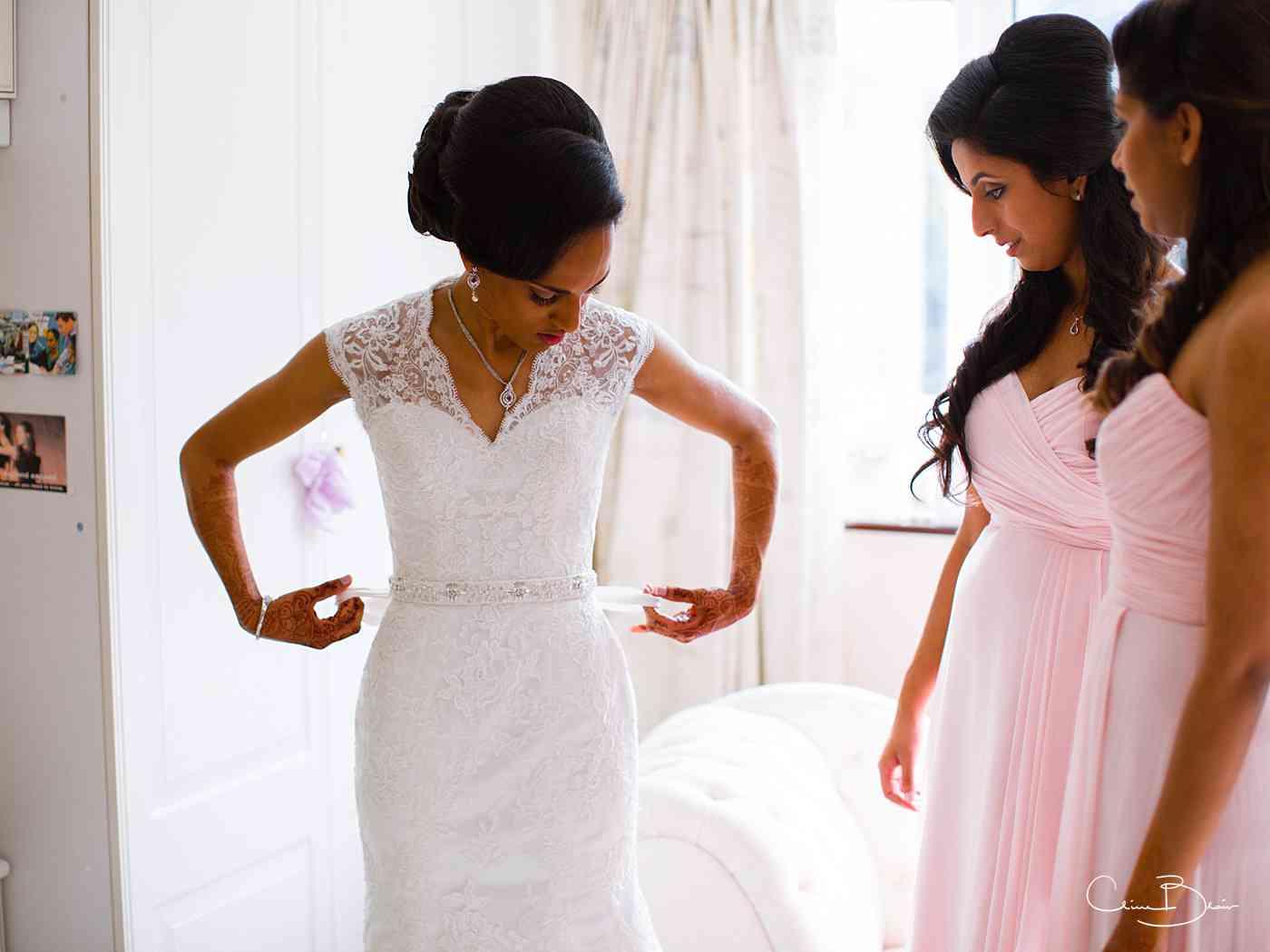 Bride making her final adjustemtns before her Ragley Hall Indian wedding