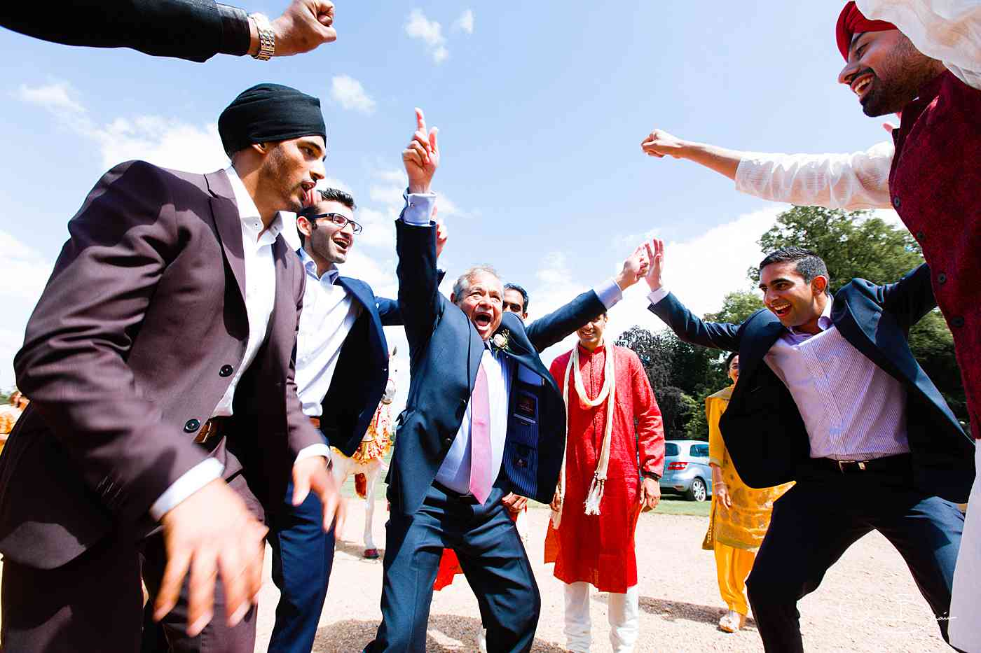 Indian guests dancing as groom arrives for wedding ceremony