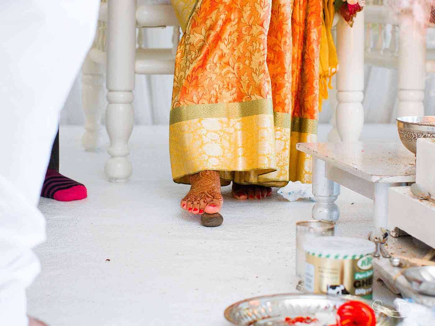 Bride stepping on stone during Hindu wedding