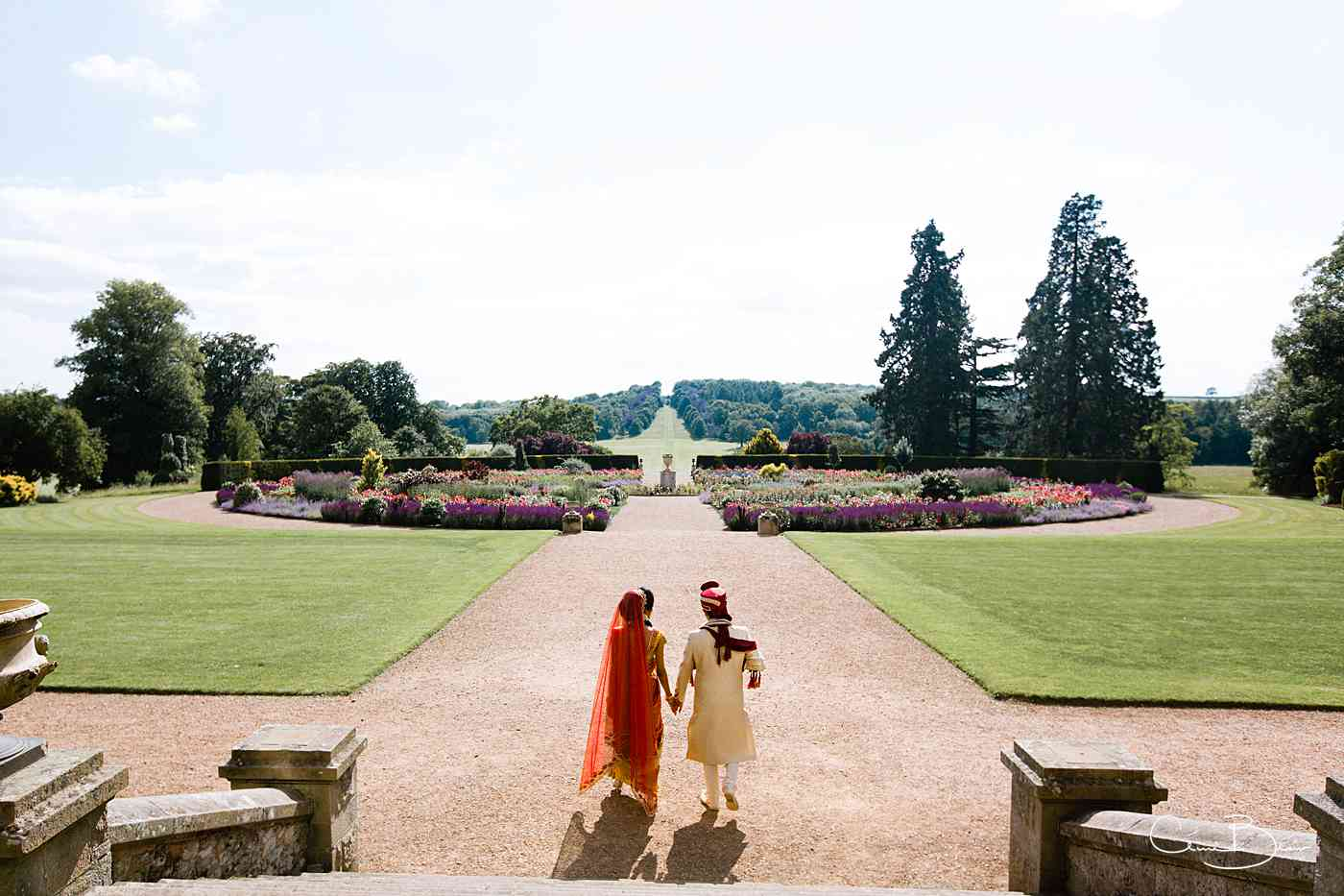 Indian bride and groom walking in grounds of Ragley Hall