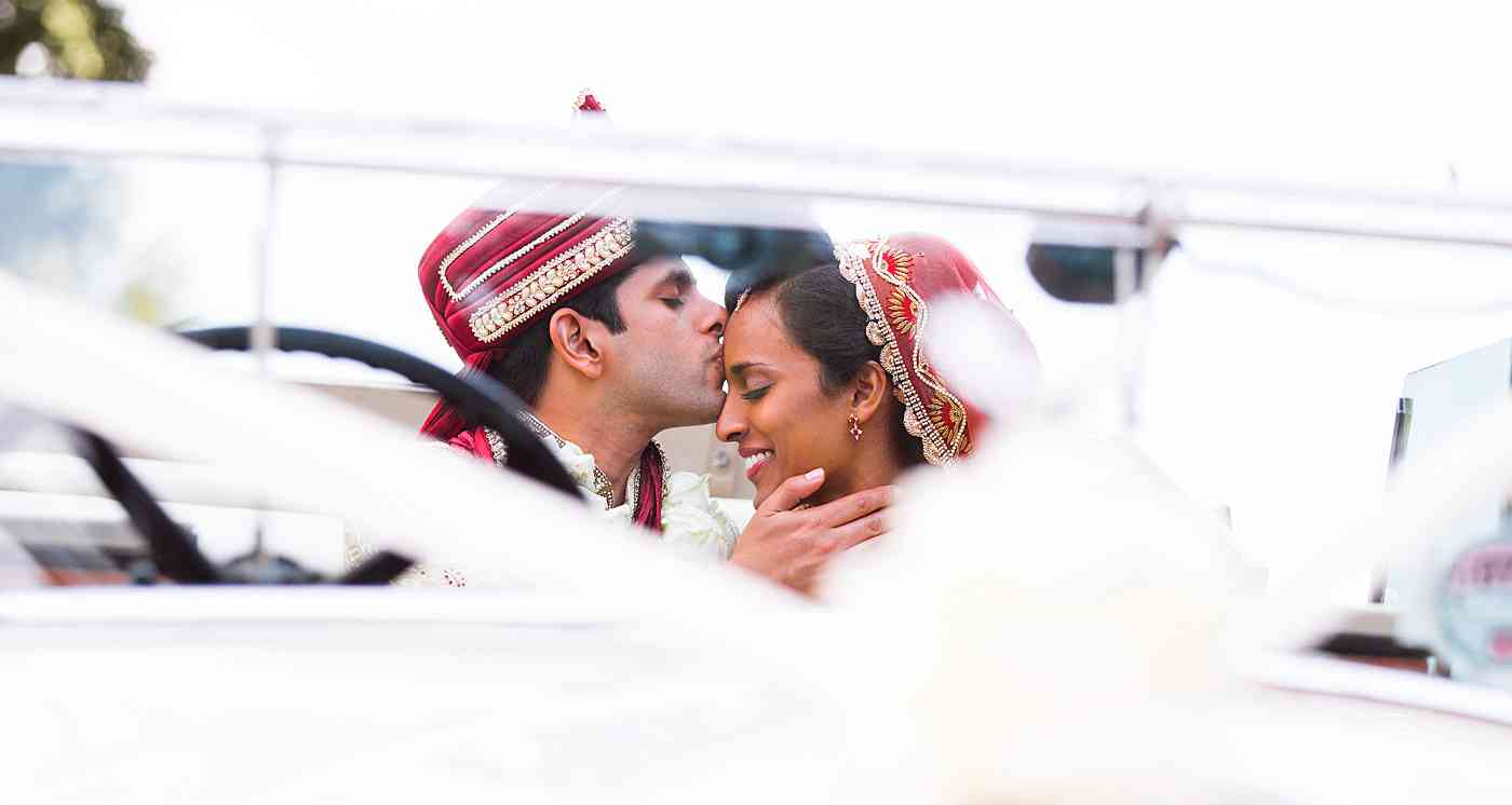 Groom kissing bride on forehead in their wedding car