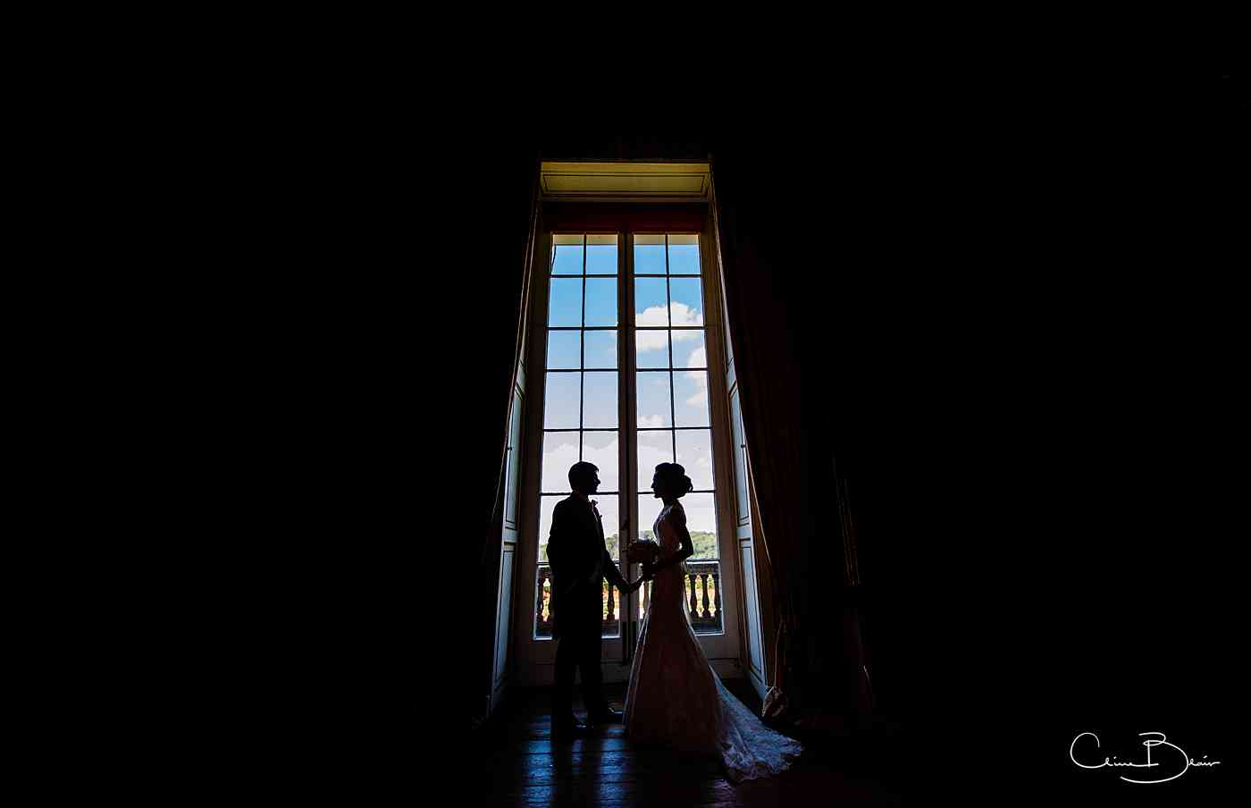Bride and groom in silhouette by Ragley Hall window
