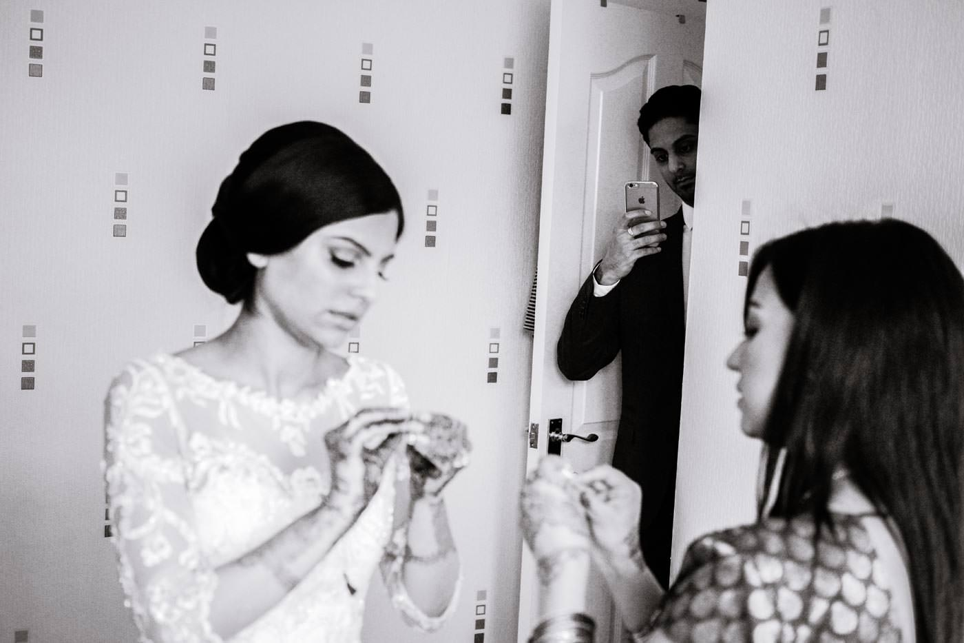 Indian bride getting ready while being photographed by her brother