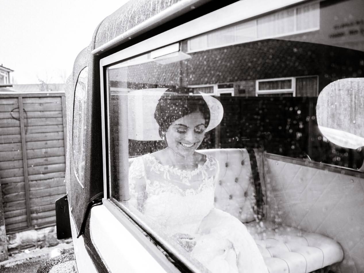 Happy Indian bride smiling in her wedding car on the way to her wedding