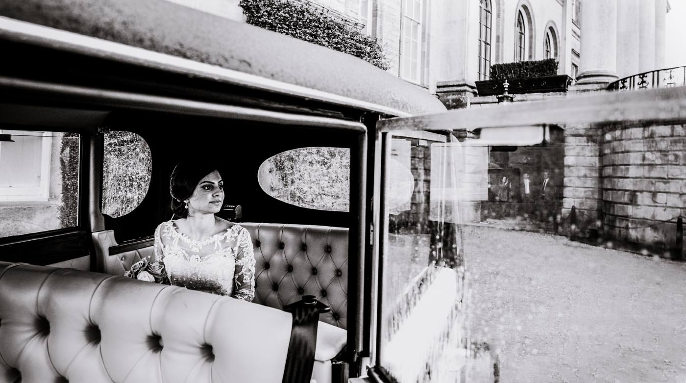 Indian bride waiting outside Ragley Hall in the car
