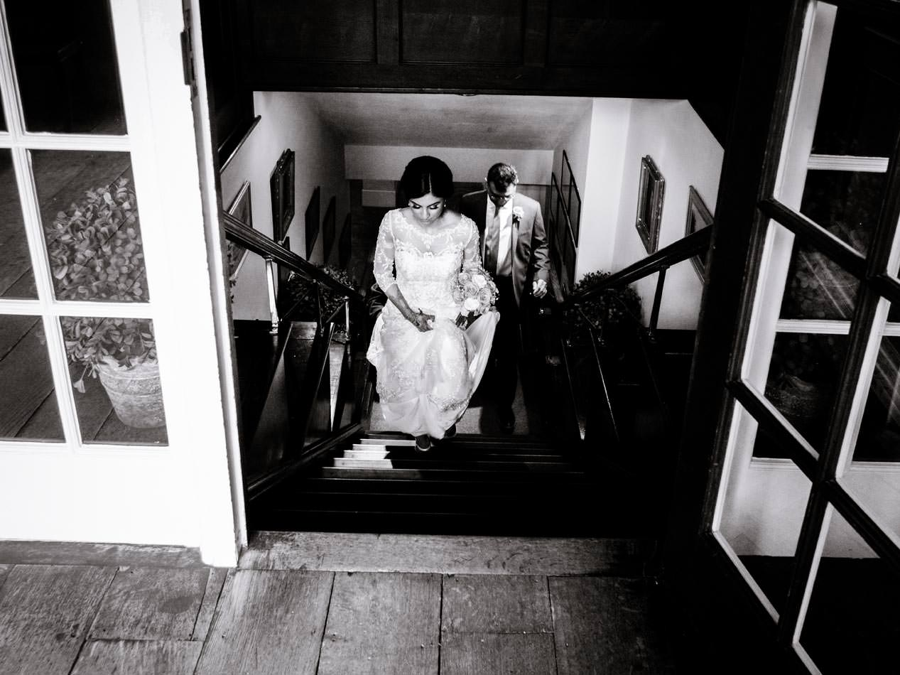 Indian bride walking upstairs in Ragley hall on the way to her wedding