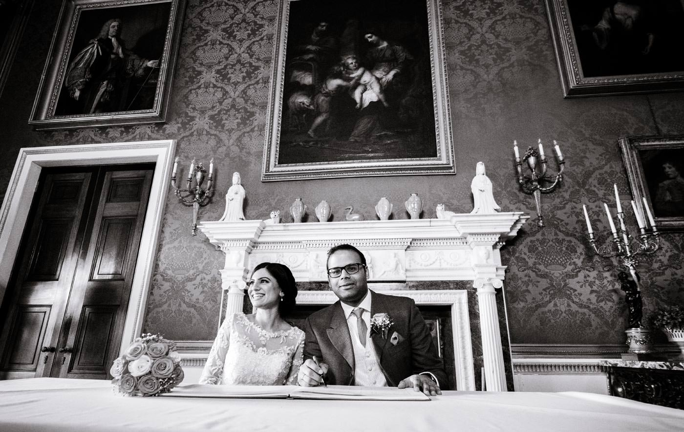 Happy Indian bride and groom signing the register after their ceremony at Ragley Hall