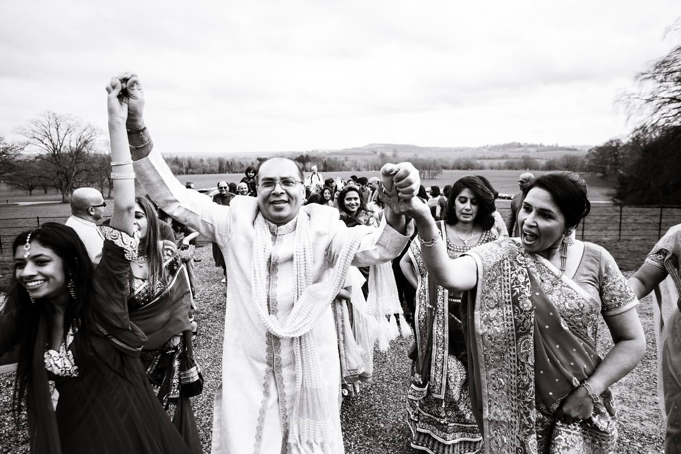Happy family and guests' procession ahead of a groom on a horse for his Hindu wedding at Ragley Hall