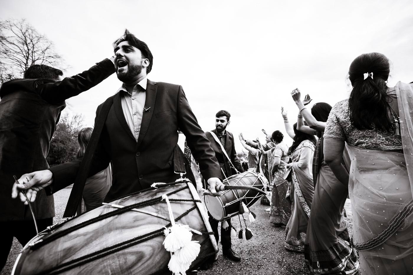 Dhol drummers, family and guests' procession ahead of a groom on a horse for his Hindu wedding at Ragley Hall