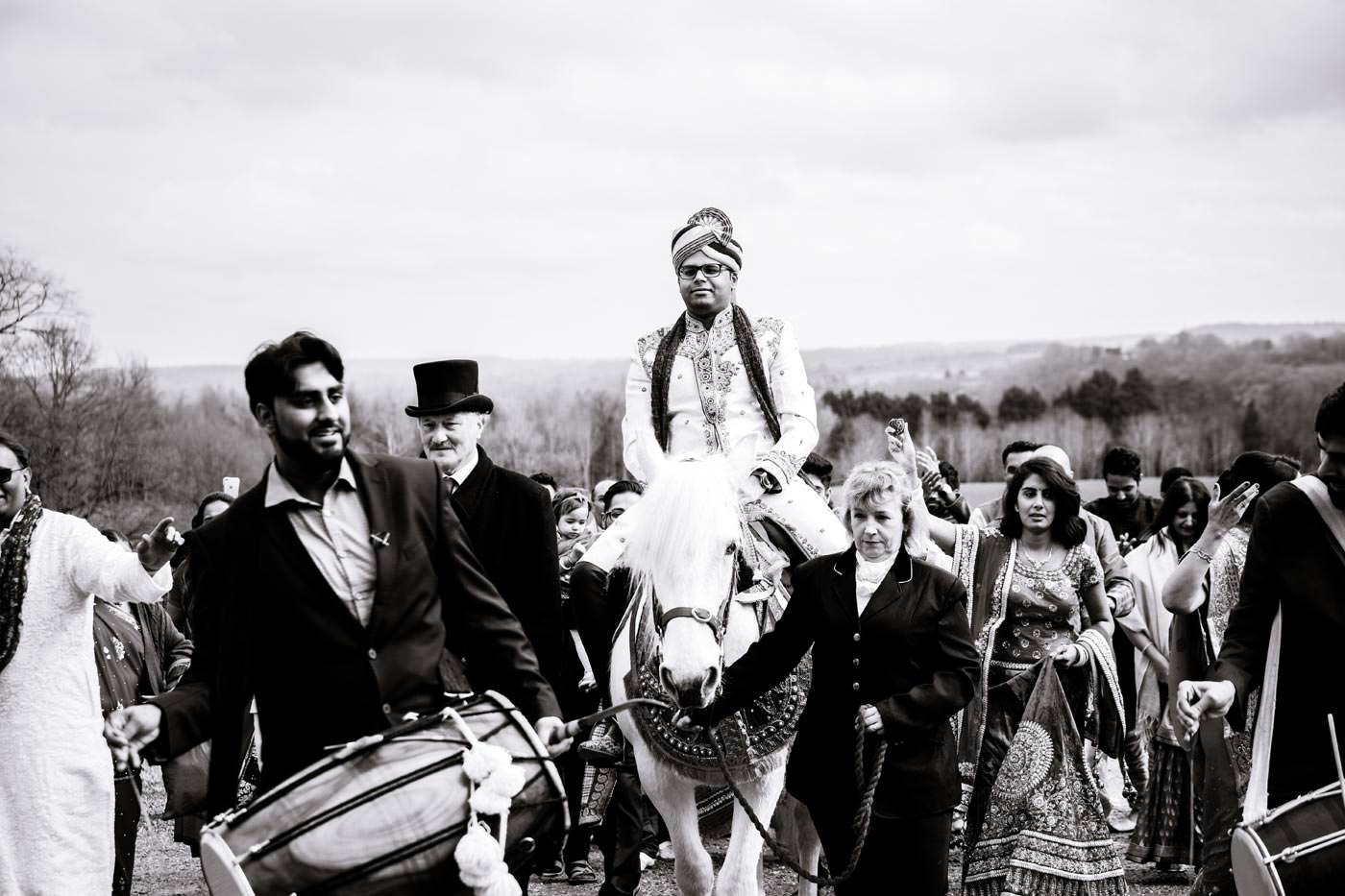 Groom on a horse arriving for his Hindu wedding at Ragley Hall