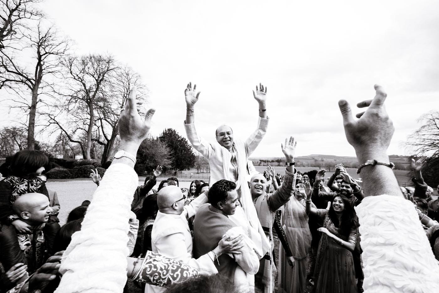 Groom's family member being held aloft as groom arrives for wIndian wedding at Ragley Hall