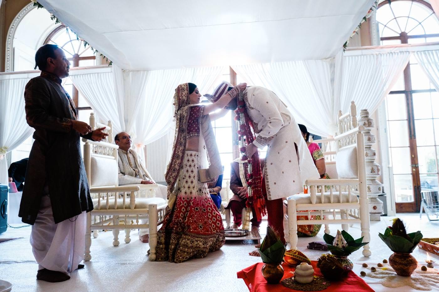Bride and groom exchanging garlands at Hindu wedding at Ragley Hall