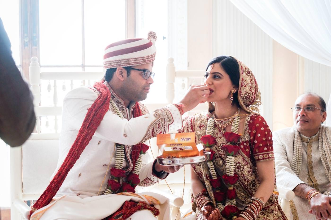 Groom feeding bride at Hindu wedding ceremony at Ragley Hall