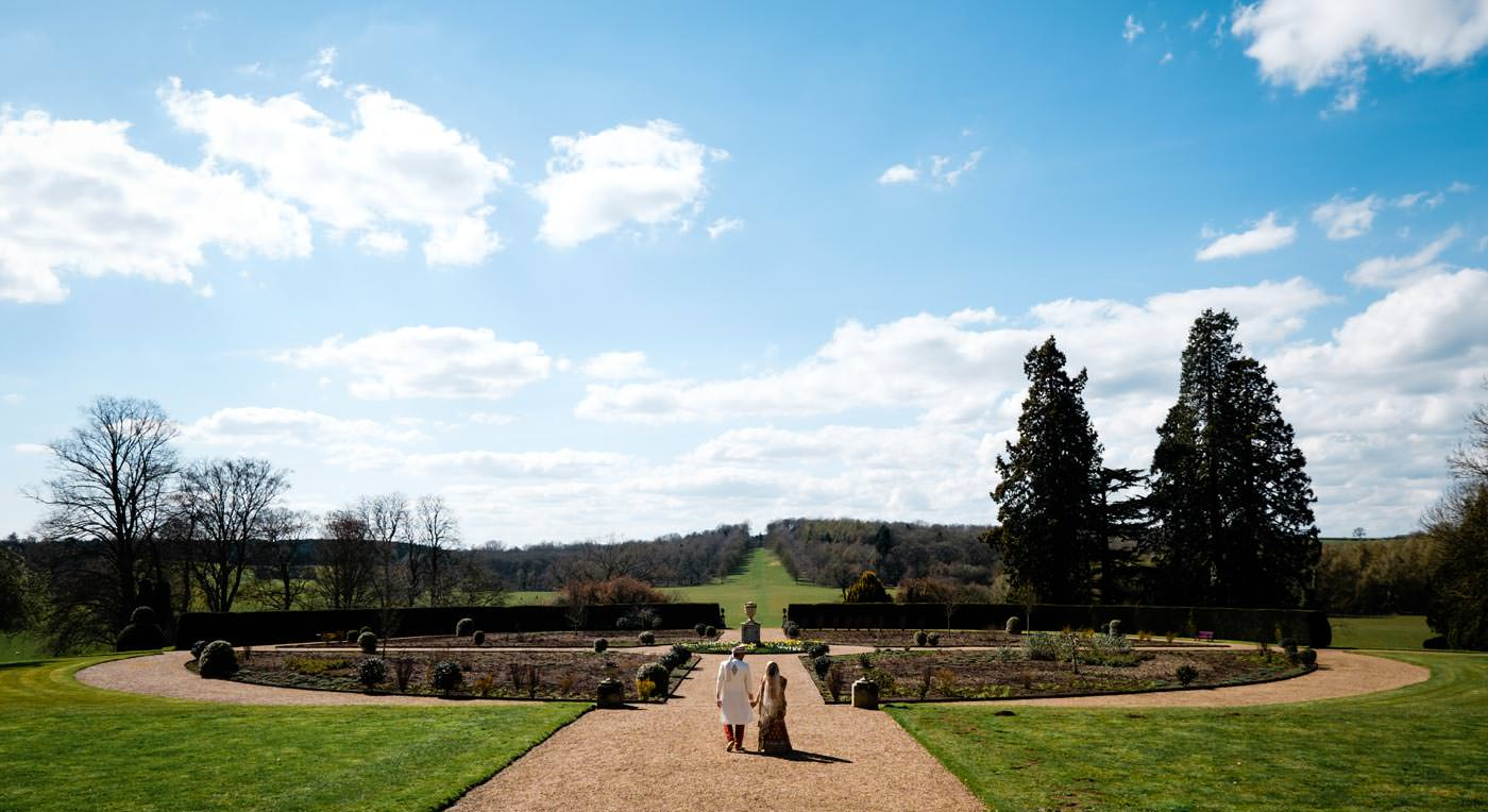 Indian bride and groom walking along the gardens at Ragley Hall