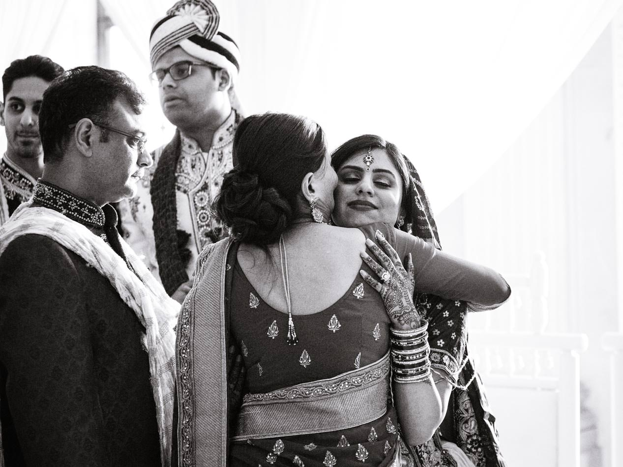 Tearful bride saying goodbye to her mother