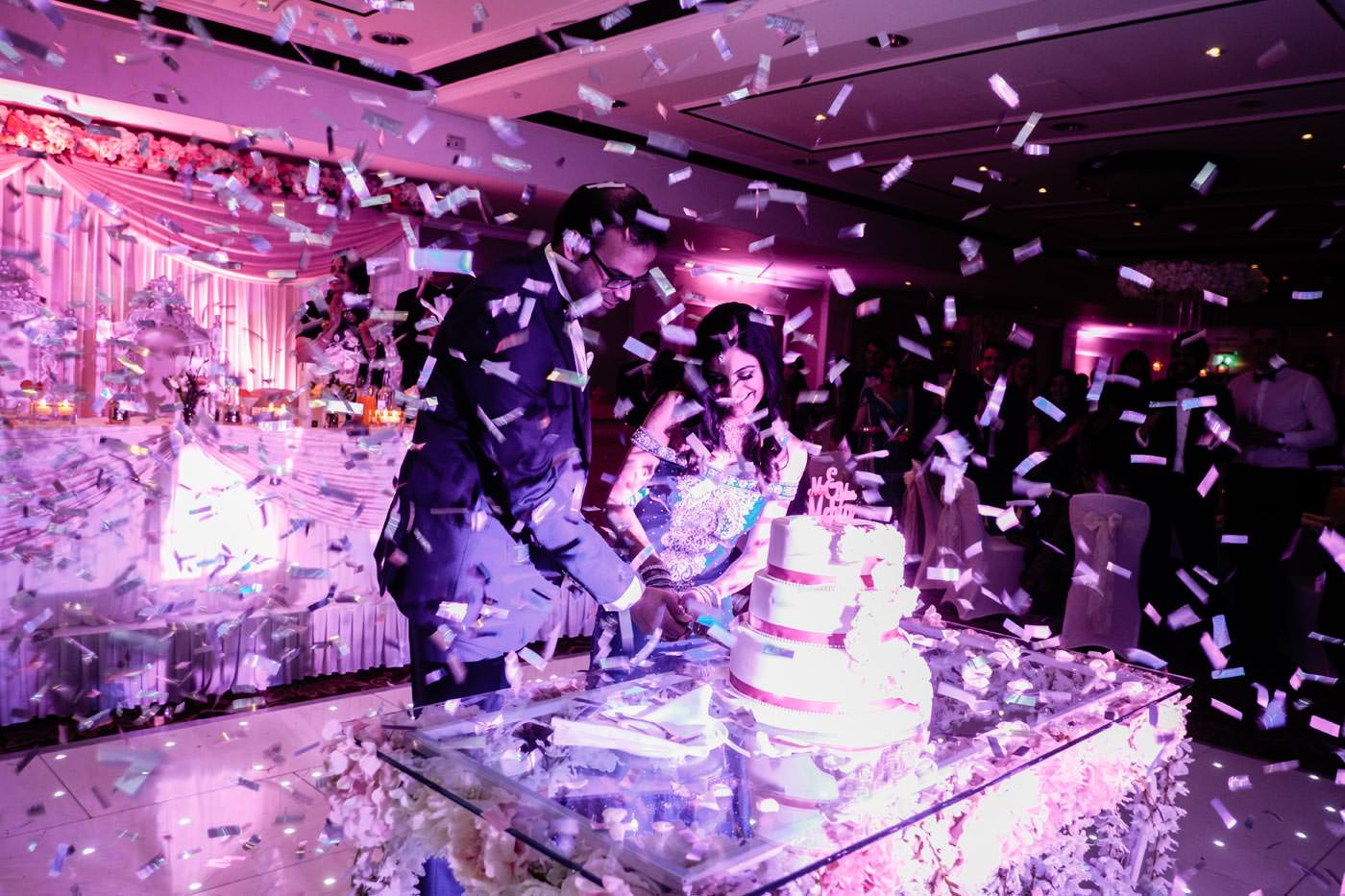 Indian brid eand groom cutting cake with confetti from confetti cannon