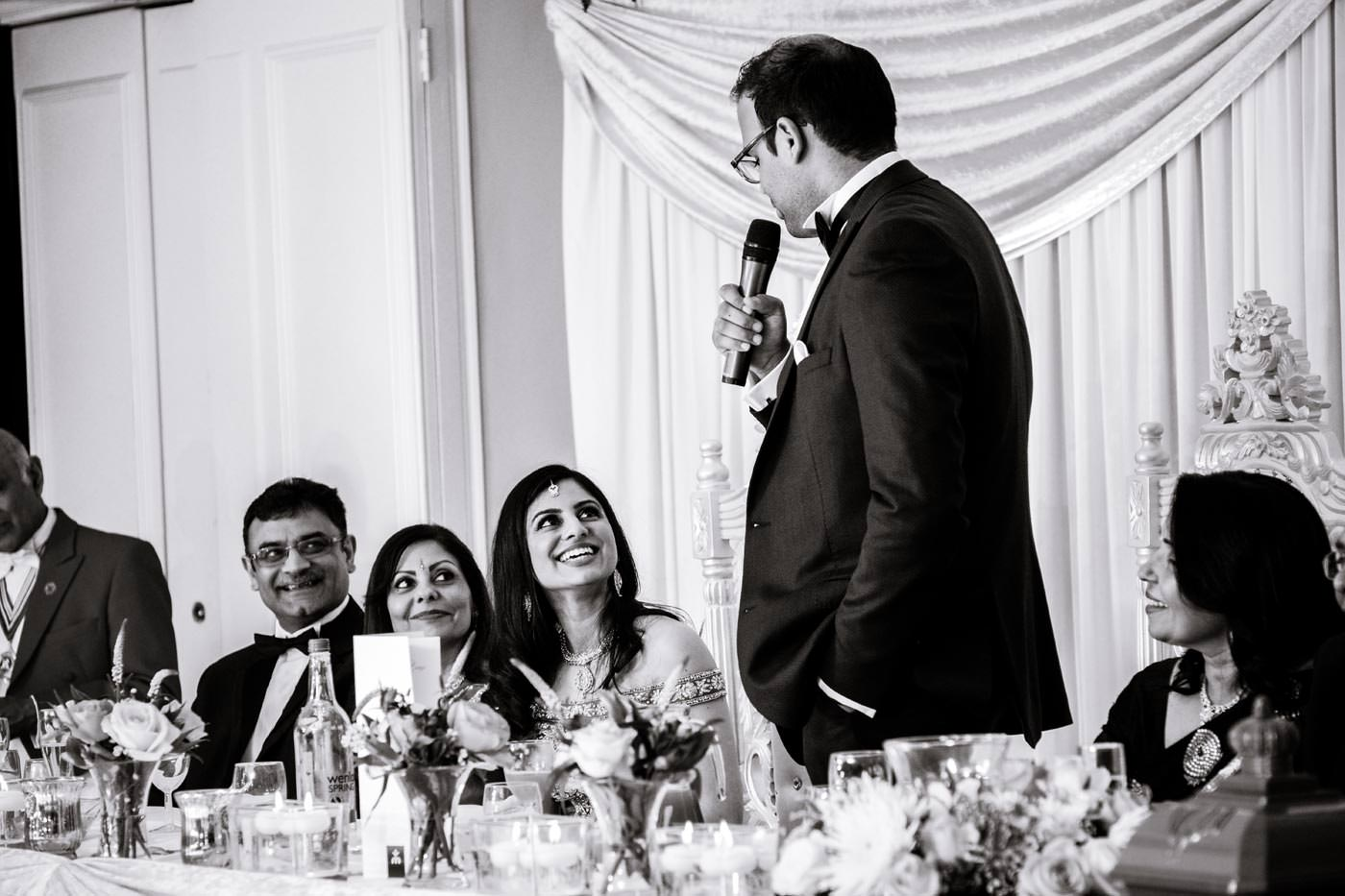 Indian groom giving a speech while being watched by bride and her family