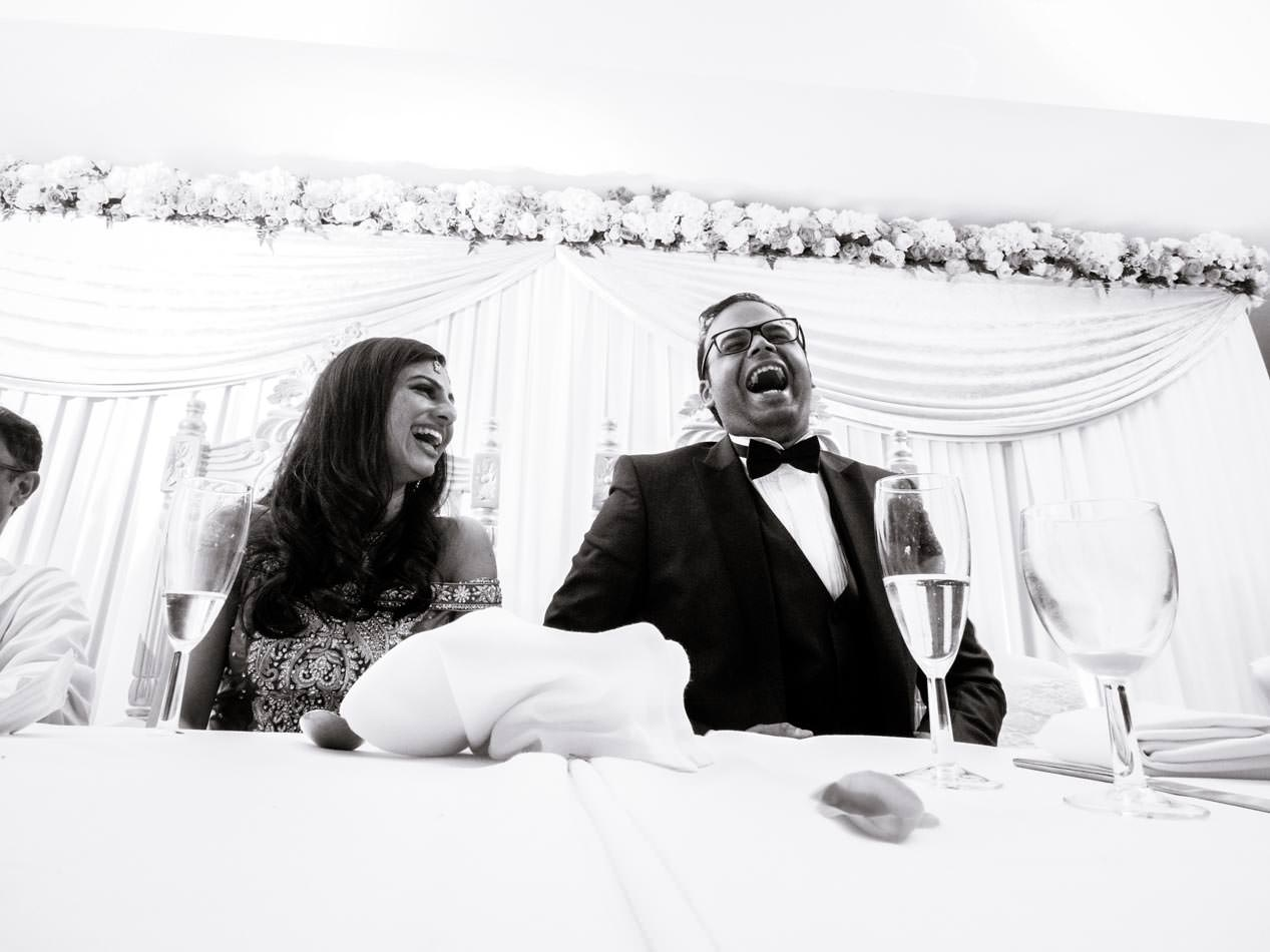 laughing Indian groom during the speeches