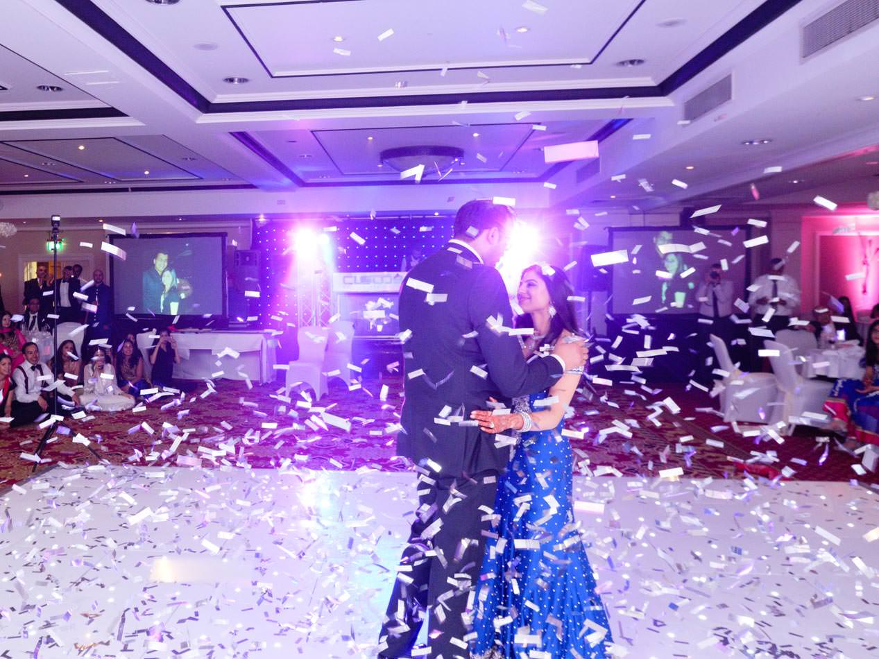 Indian bride and groom during rheir first dance surrounded by confetti from a confetti canon