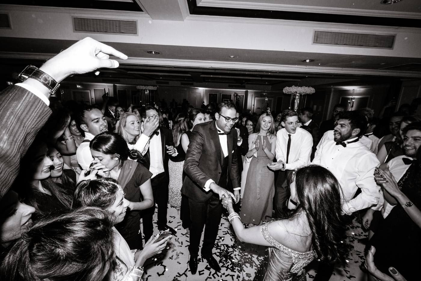 Indian bride and groom dancing surrounded by guests