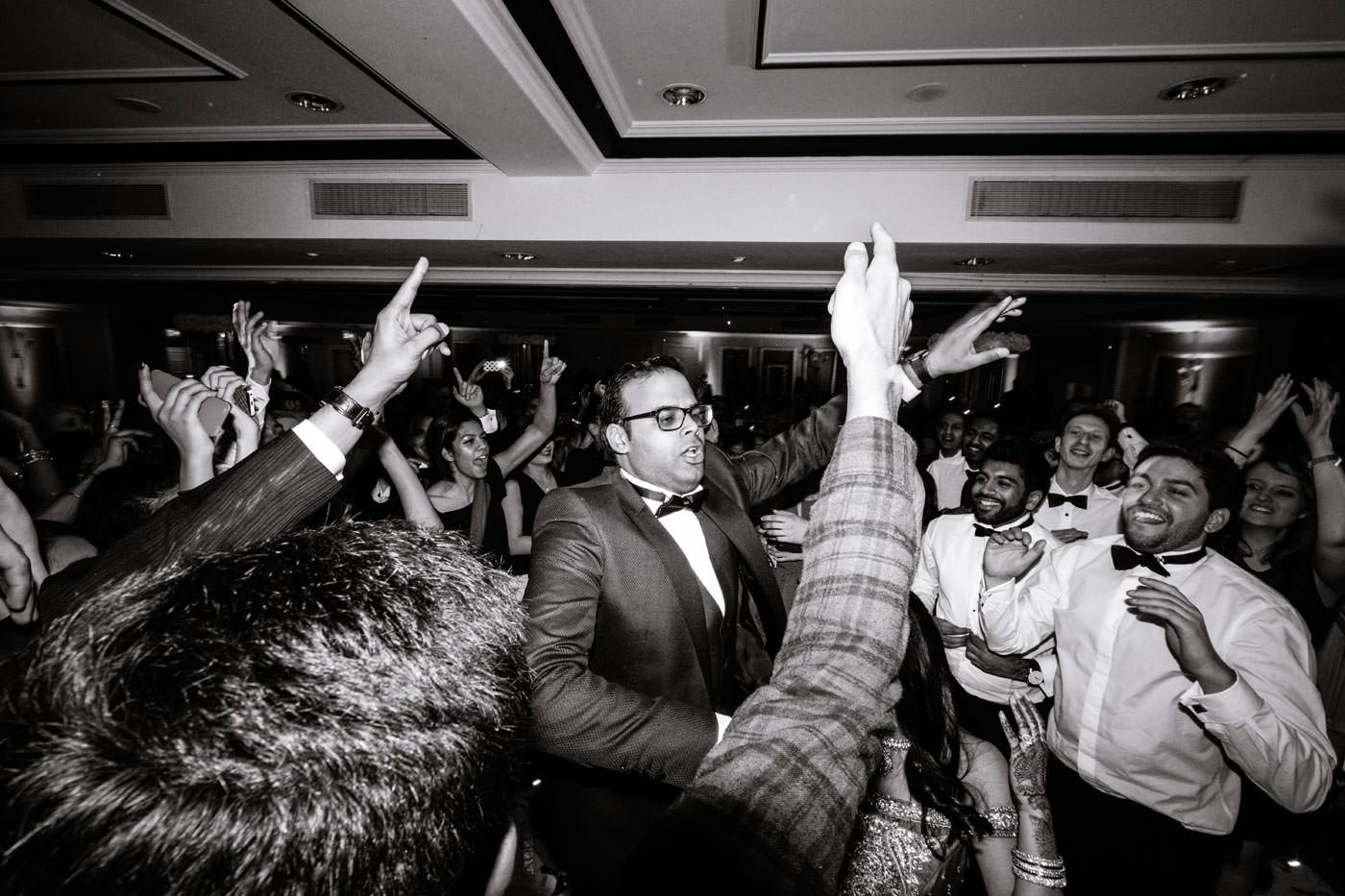 Indian groom dancing surrounded by guests