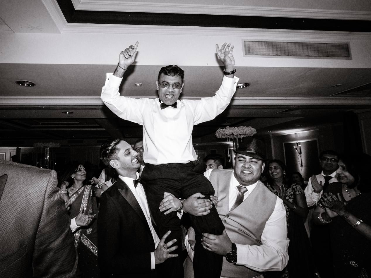 Indian father of bride being help aloft by family friends