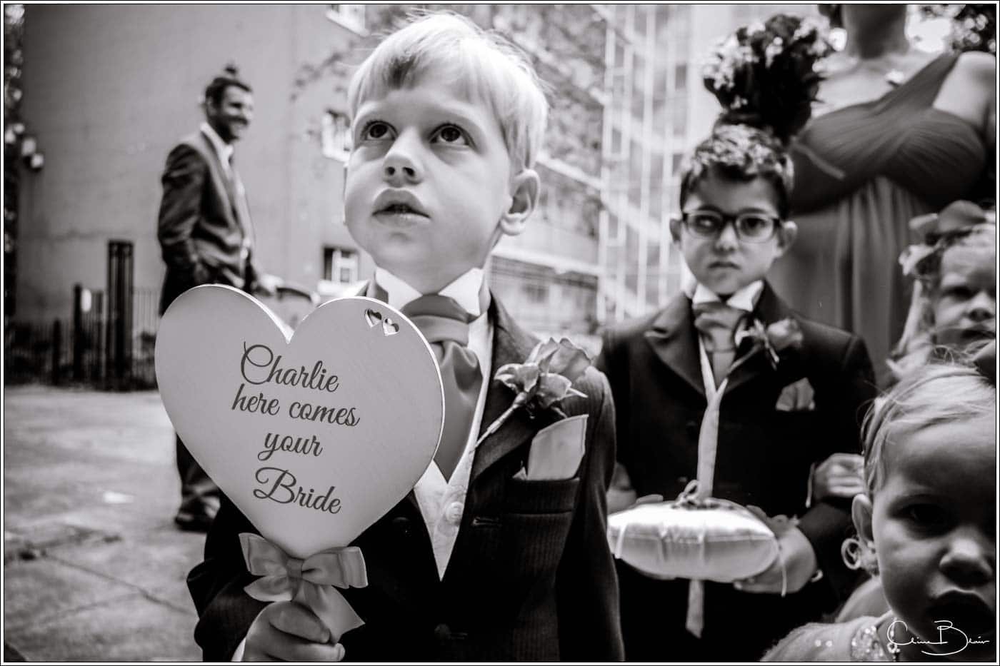 "pageboy holding ""here comes the bride"" sign before a botleys mansion wedding reception"