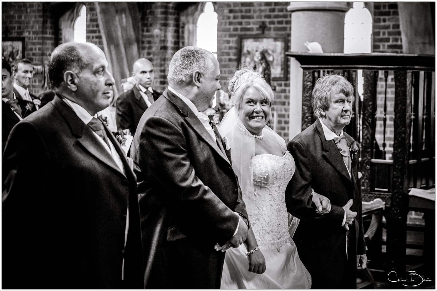 bride smiling at the groom at the alter before their botleys mansion wedding reception