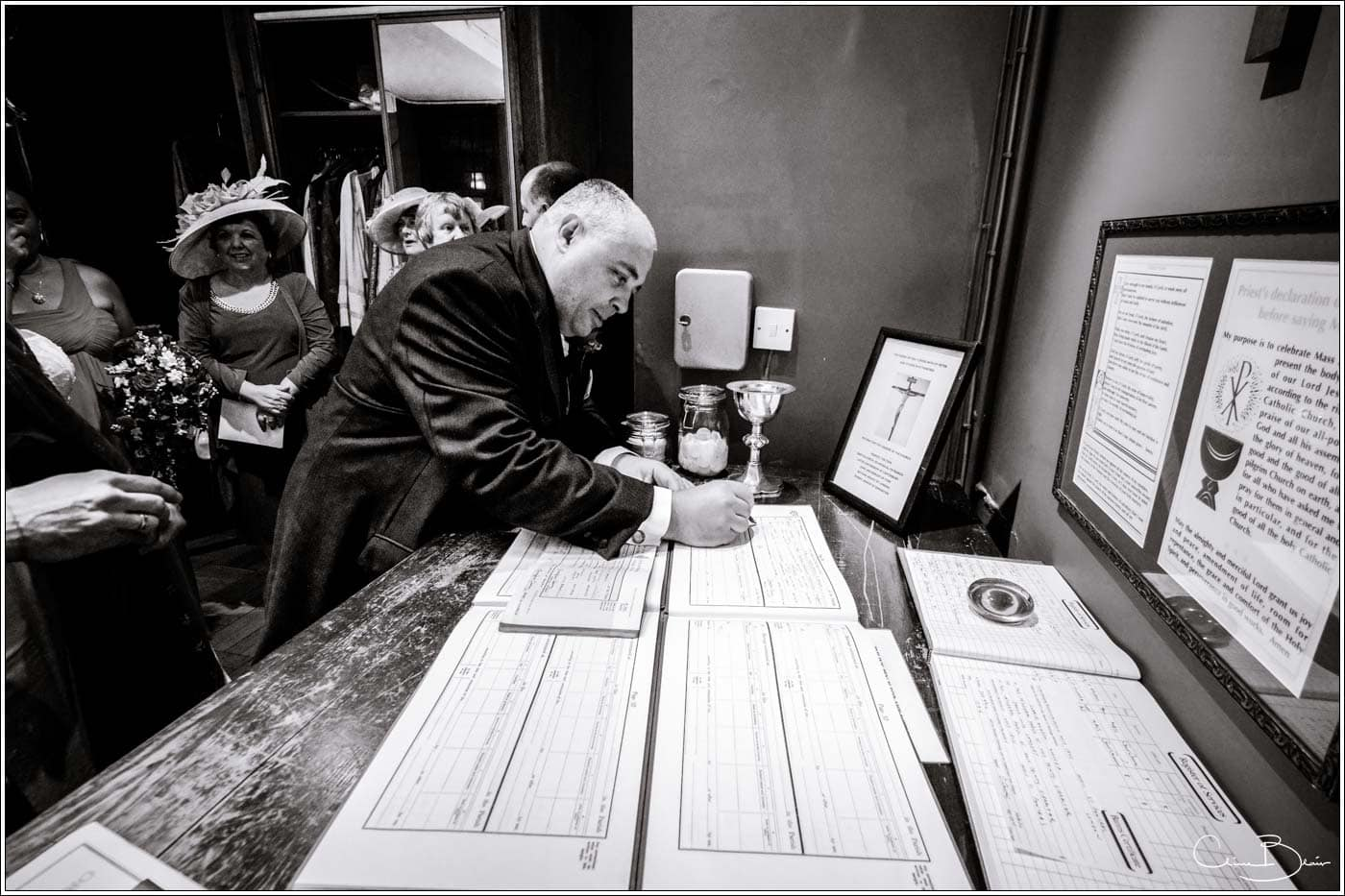 groom siging the register before his botleys mansion wedding reception