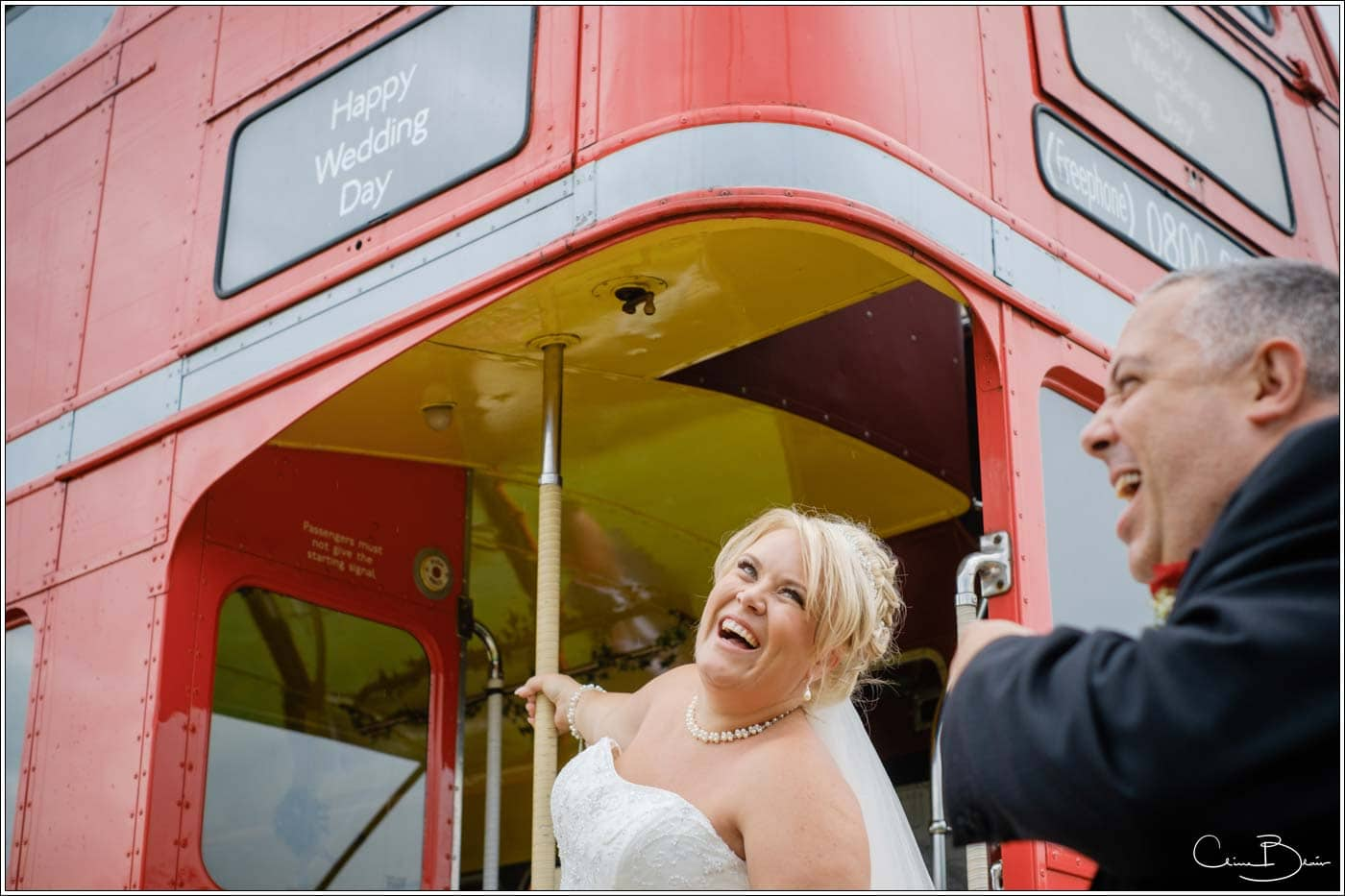 happy bride and groom by a red double decker bus at their botleys mansion wedding reception