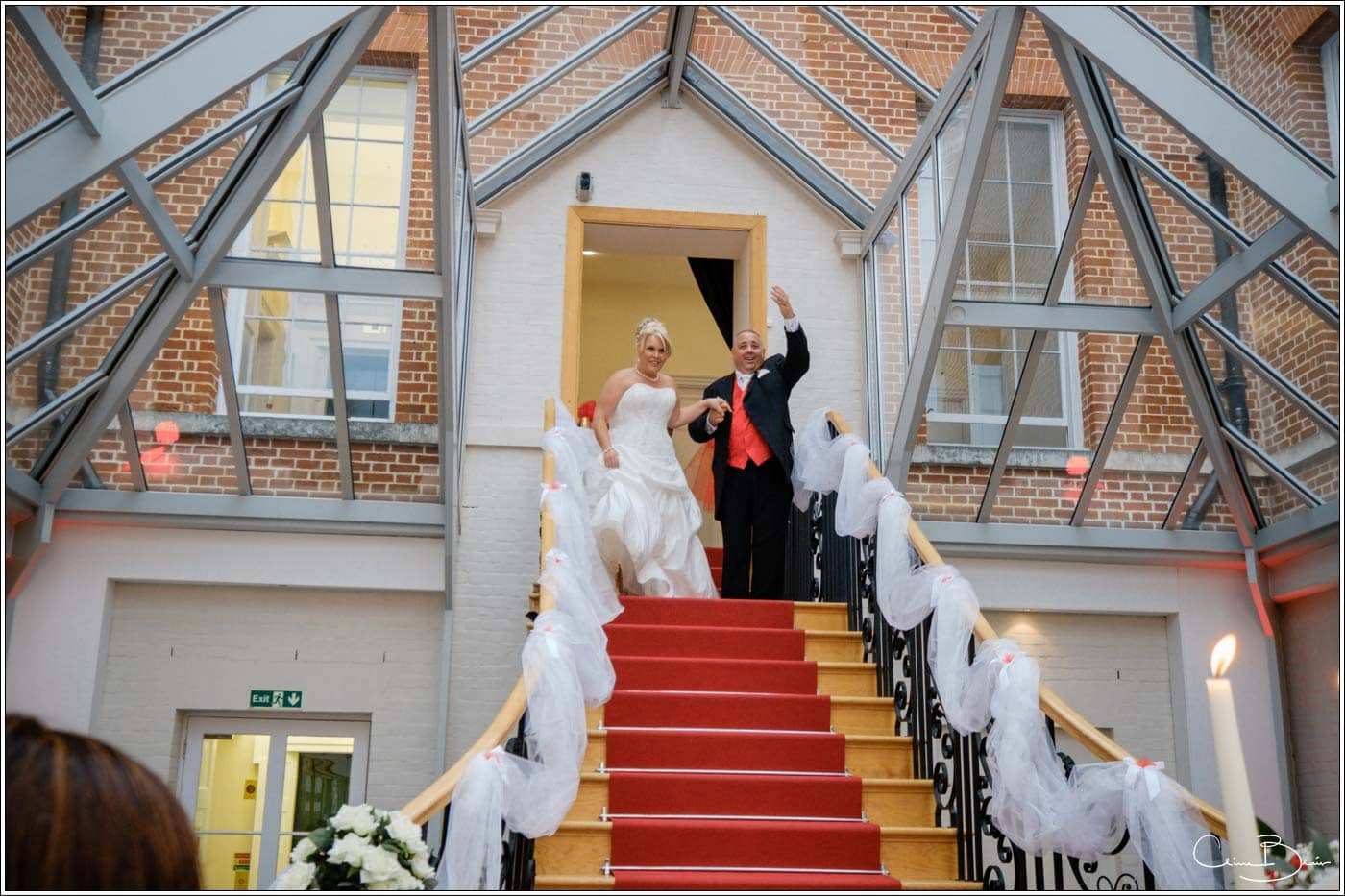 Bride and groom descending their stairs for their Botleys Mansion wedding reception