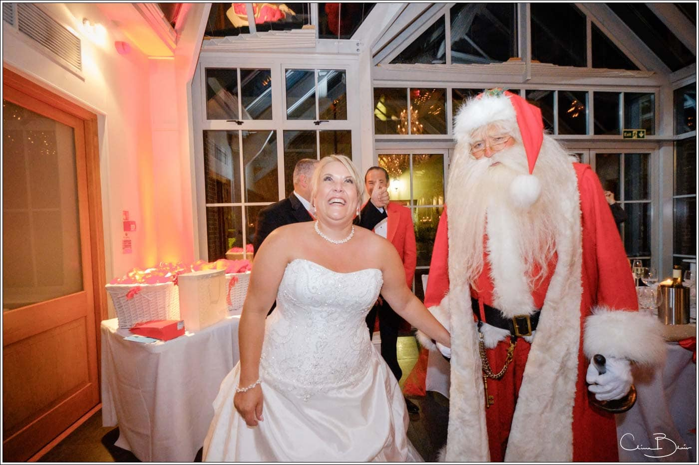 bride happy to meet father christmas in the summer at her botleys mansion wedding reception