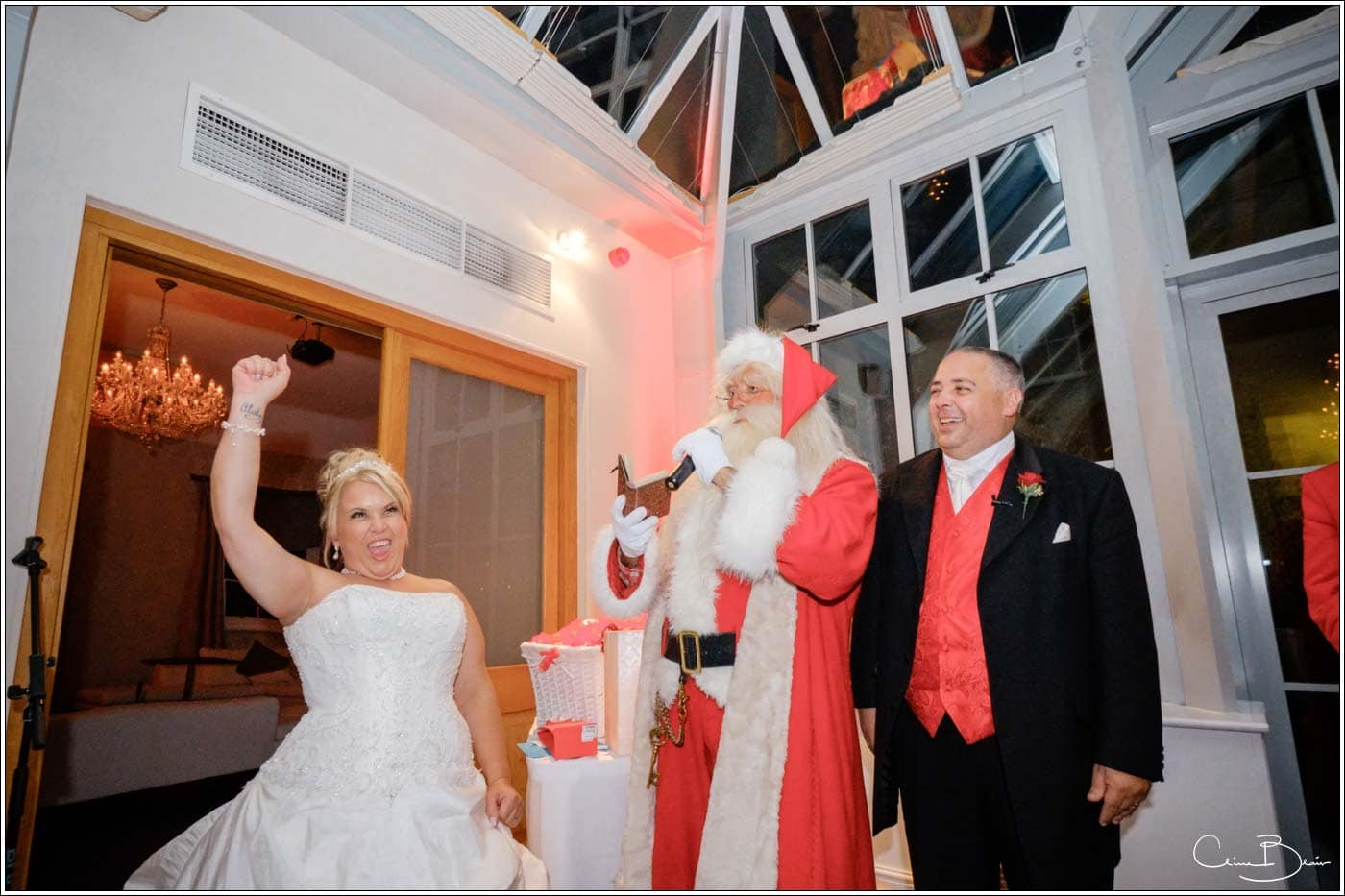 jubilant bride meeting father christmas in the summer at her botleys mansion wedding reception