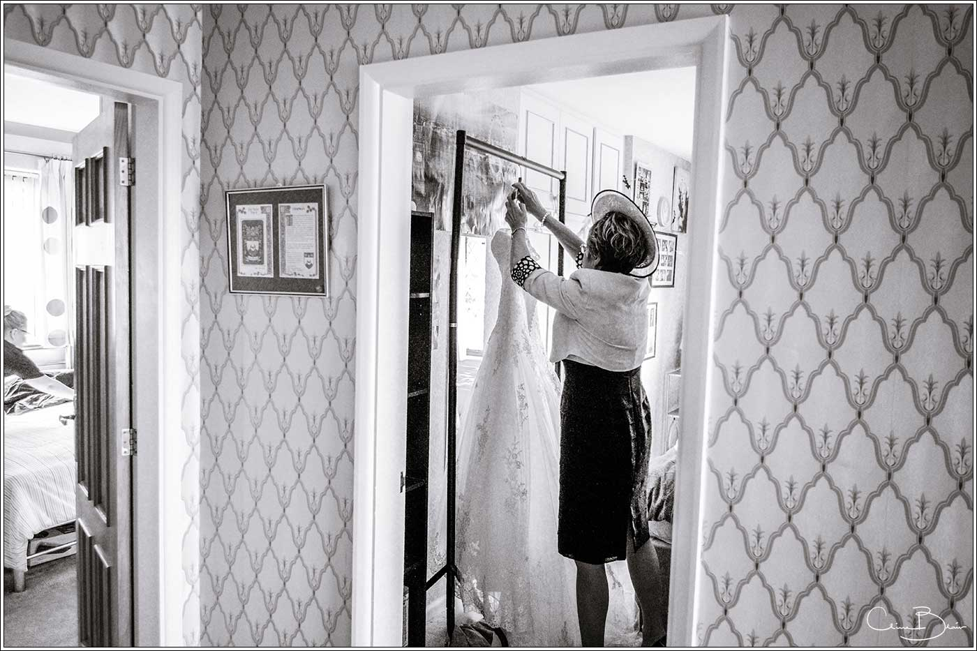 Coombe Abbey wedding photography showing mother of bride hanging up the wedding dress