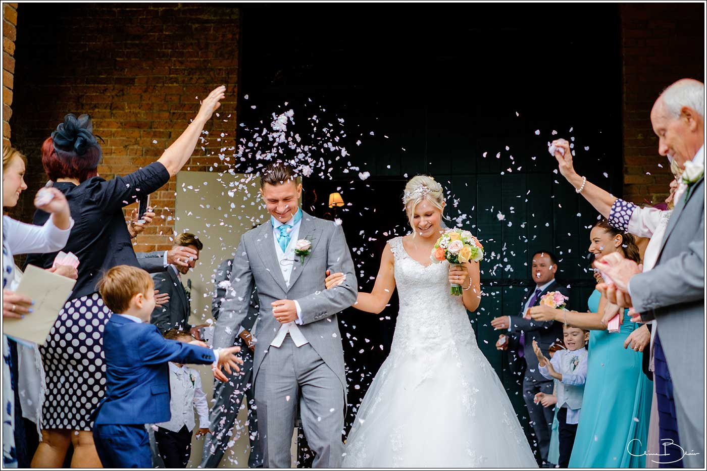 Coombe Abbey wedding photography showing bride and groom exiting abbey gate under confetti