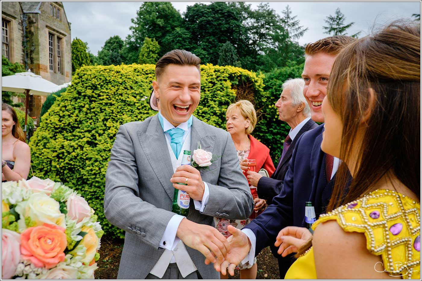 Coombe Abbey wedding photography showing groom happily greeting guests