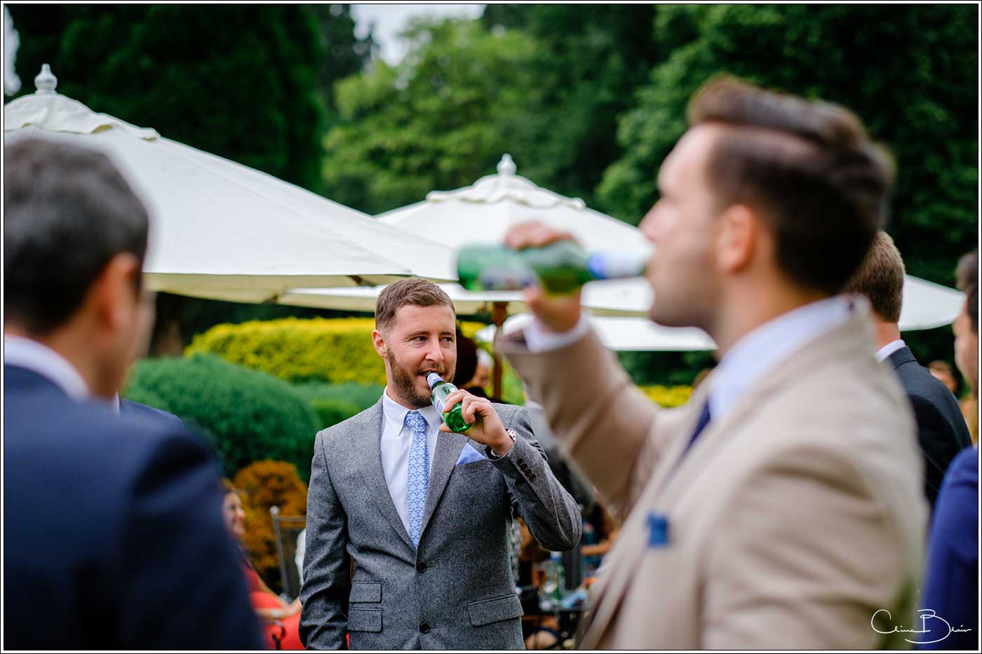 Coombe Abbey wedding photography showing men drinking during the drinks reception on the lawn