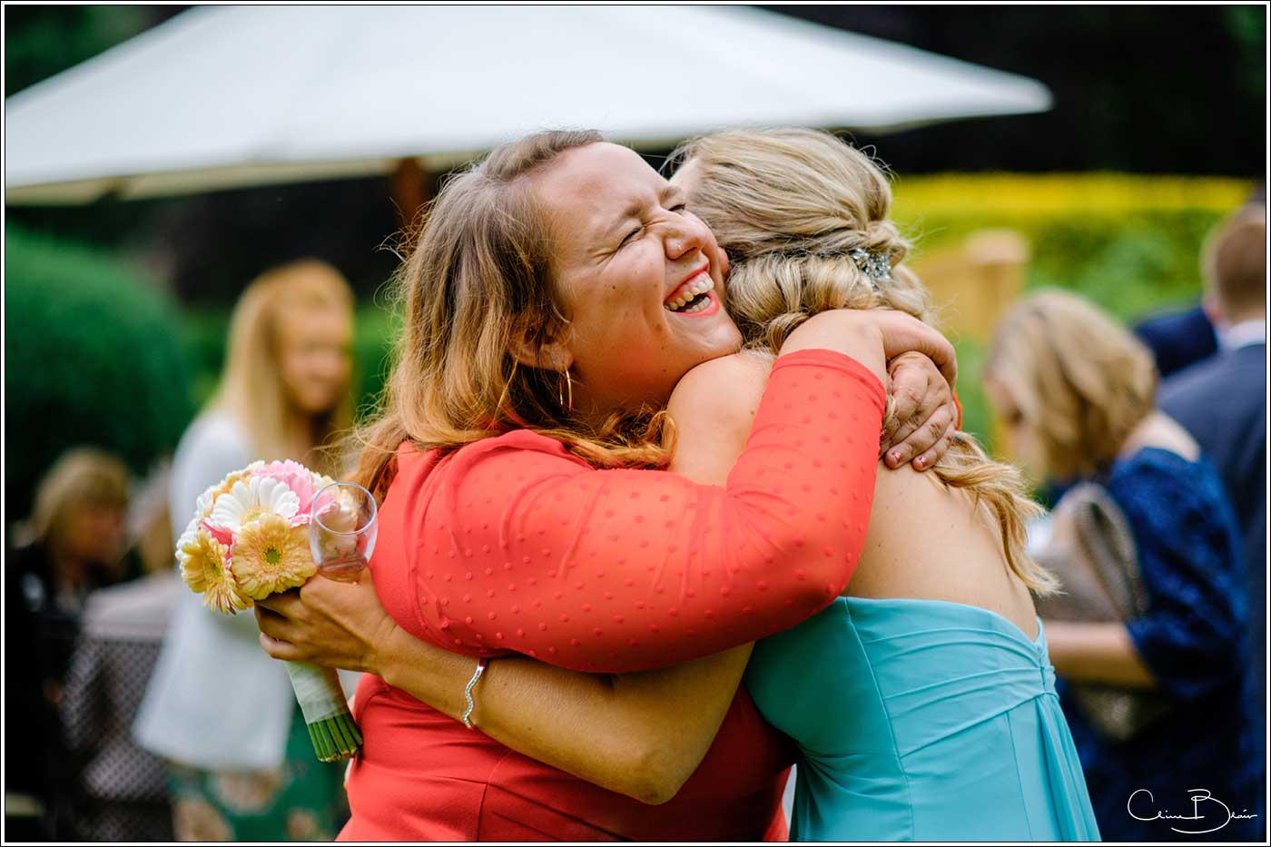 Coombe Abbey wedding photography showing 2 women guest hugging each other while laughing