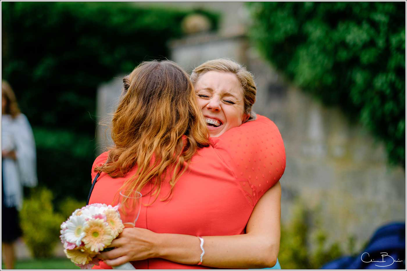 Coombe Abbey wedding photography showing 2 women guest hugging each other laughing