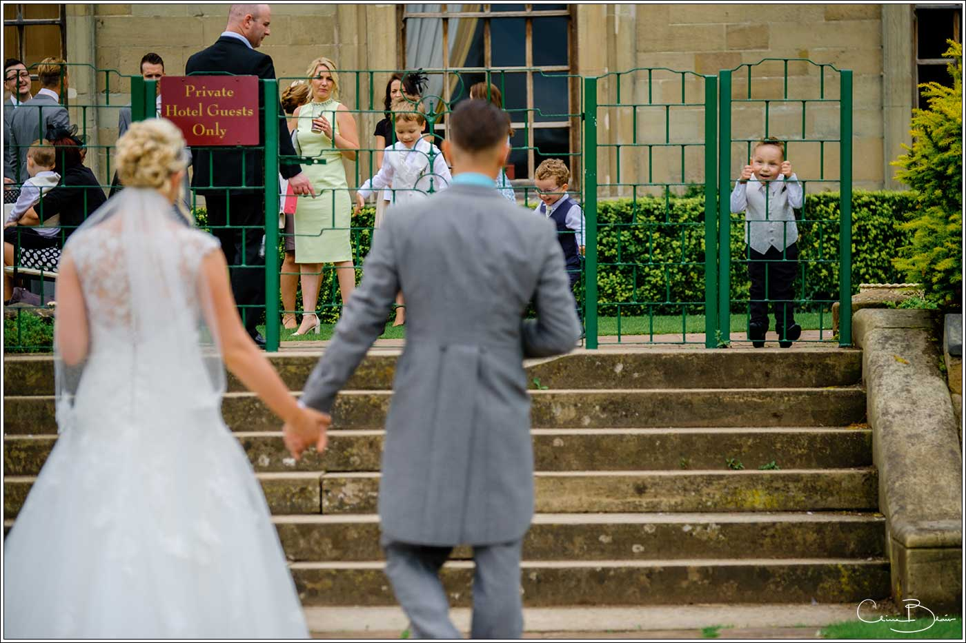 Coombe Abbey wedding photography showing bride and groom walking toward children looking on