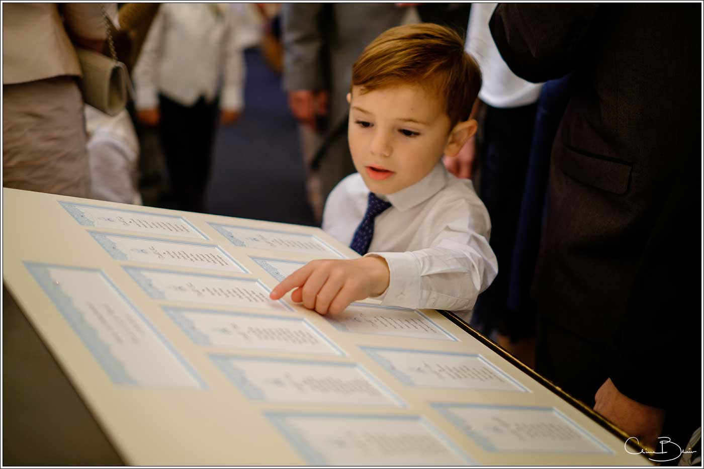 Coombe Abbey wedding photography showing child spotting his name on the guests seating plan