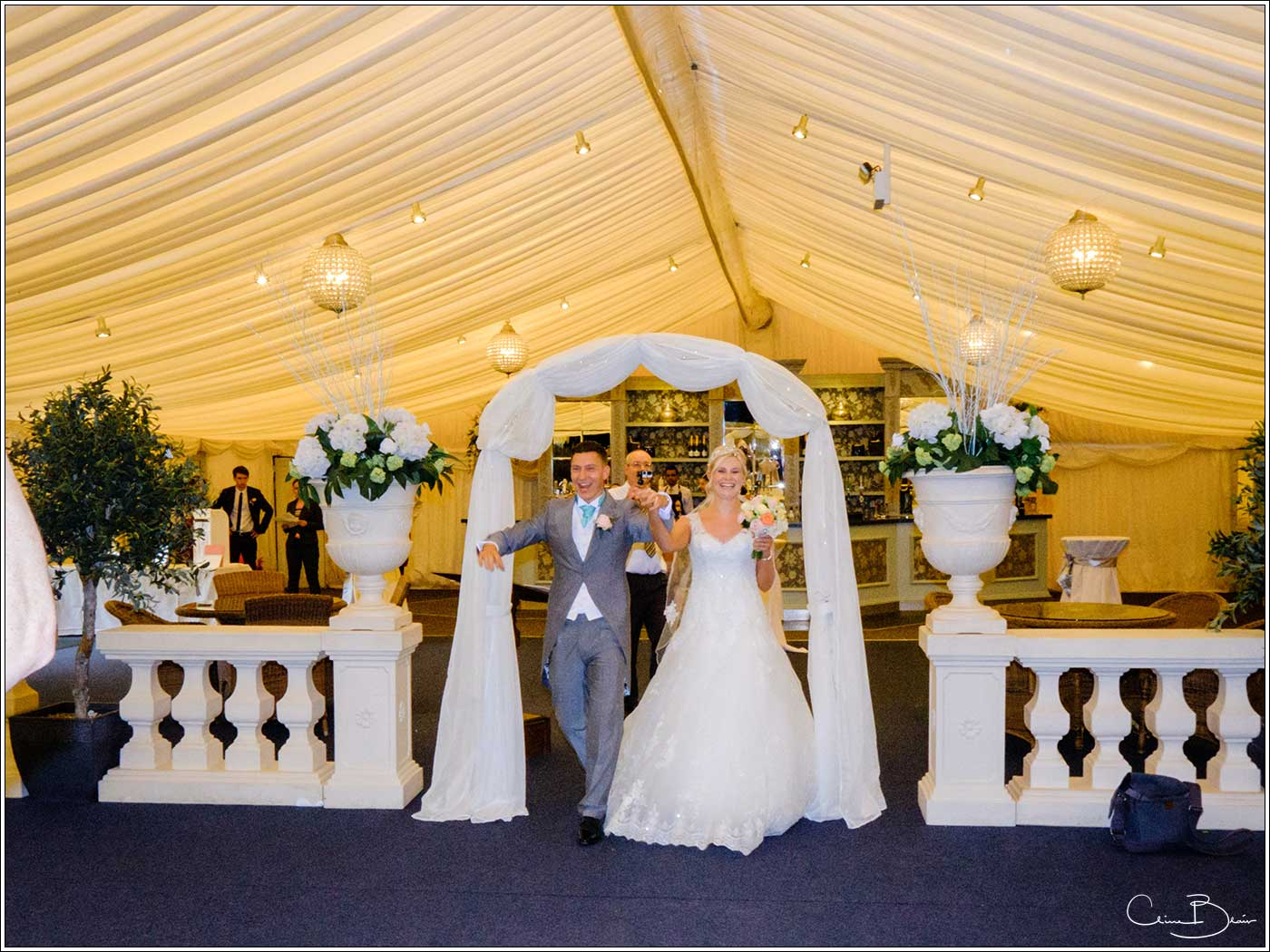 Coombe Abbey wedding photography showing happy bride and groom being welcomed in for their wedding breakfast