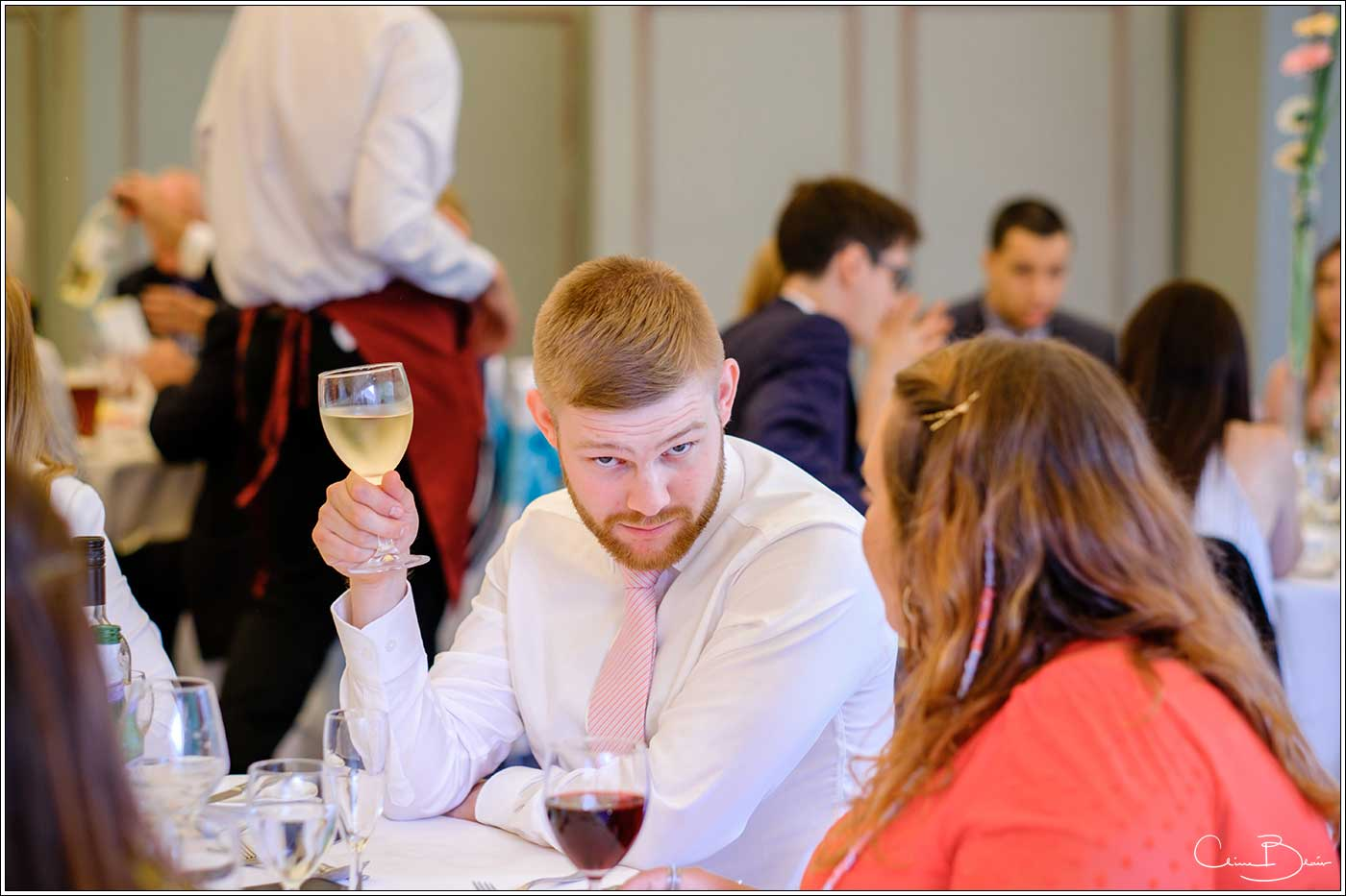 Coombe Abbey wedding photography showing man with glass of wine looking at the camera