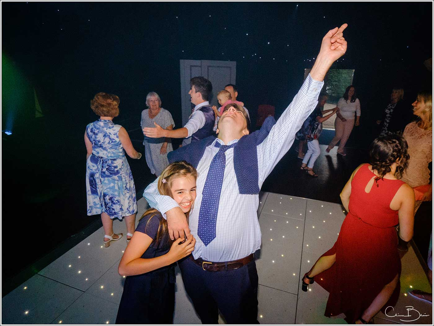 Coombe Abbey wedding photography showing man hugging a child on the dance floor